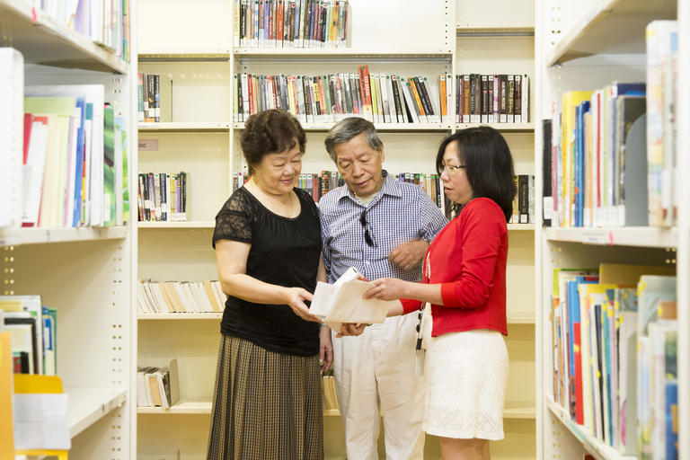 Man and two women looking at a book