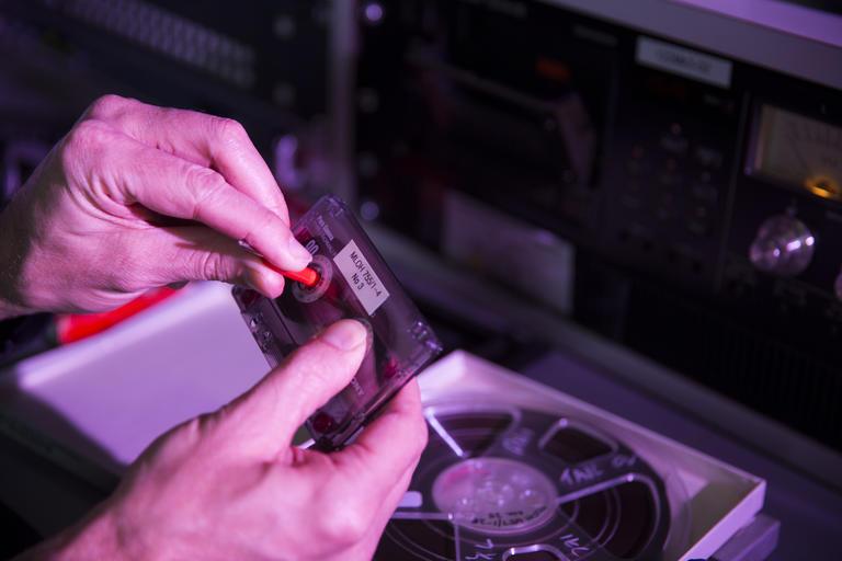 man's hands holding cassette tape