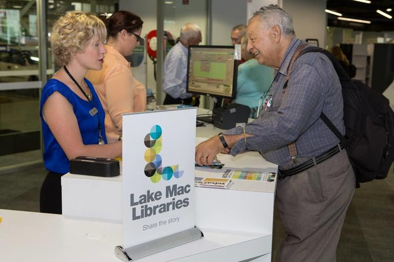 Man approaching librarian at desk - Lake Mac Libraries Cardiff branch