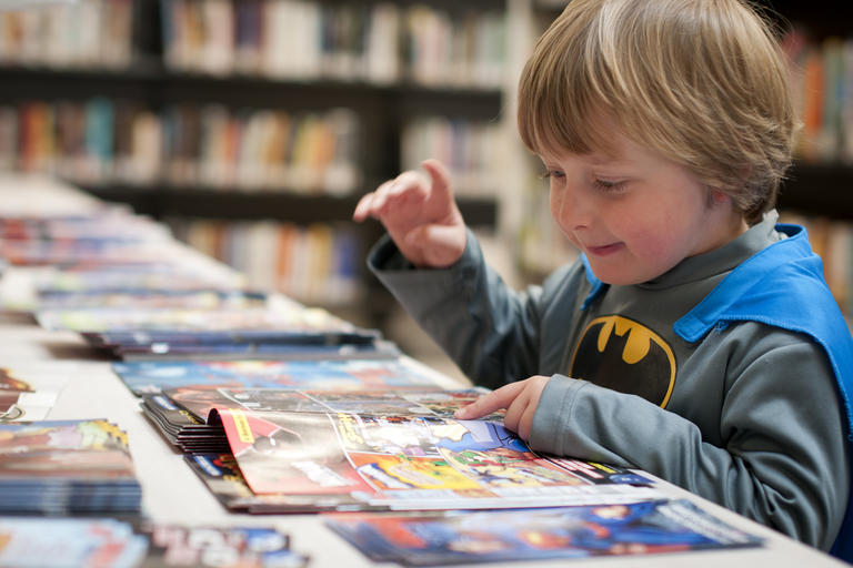Boy in Batman costume reading book