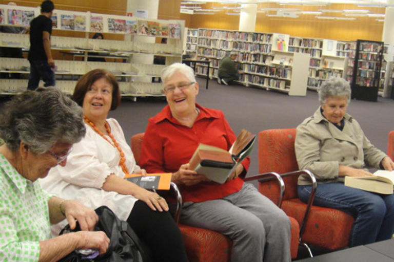 Women laughing and reading books in library - Blacktown Library