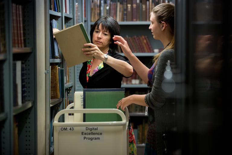 Two women sorting books in trolleys