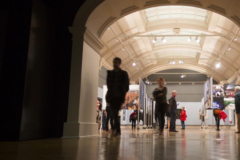 Men and women walking through dark hall