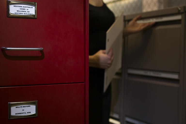 Woman standing behind red filing cabinet