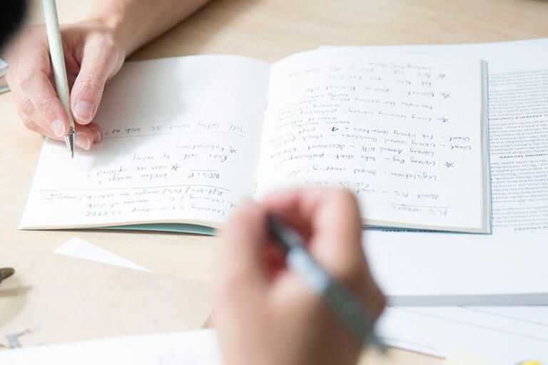 close-up view of two people at a desk with notepads and pens