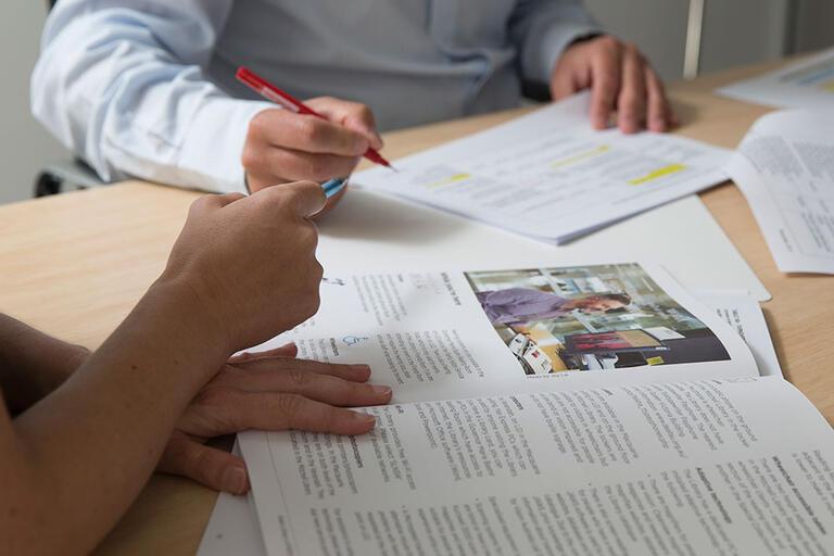 close up of peoples' hands with papers, books and pens at a desk