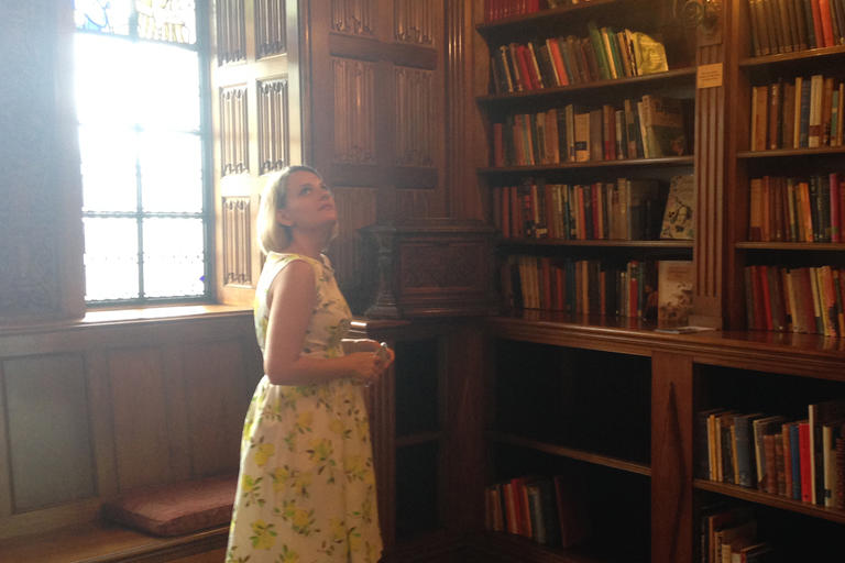 Girl looking around large booklined room