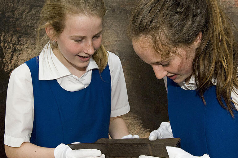 Two students looking at wooden object