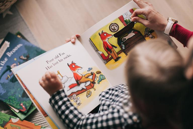 Child and adult looking at picture book