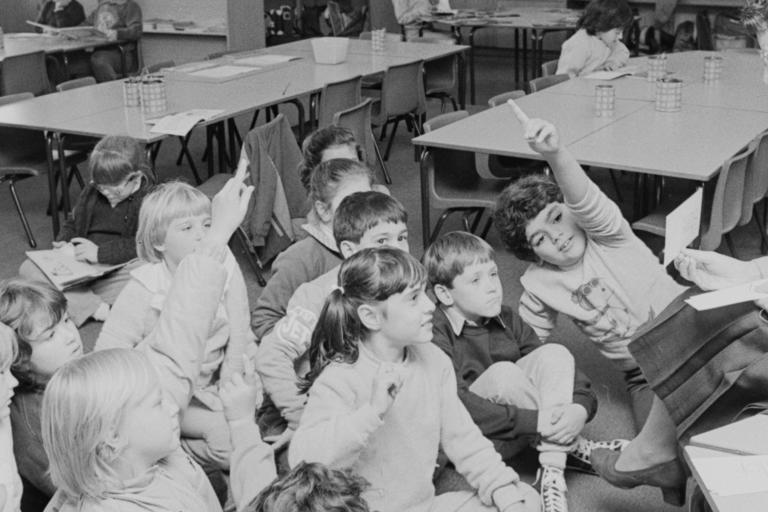 A black and white photograph of school children sitting on the school room floor with raised hands in front of their teacher.