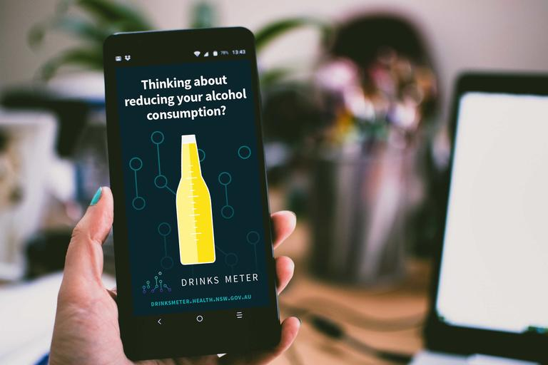 Hand holding mobile phone showing a picture of a bottle and the words drinks meter