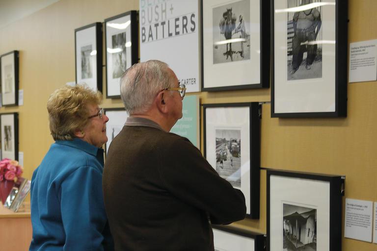 Man and woman looking at photos on wall