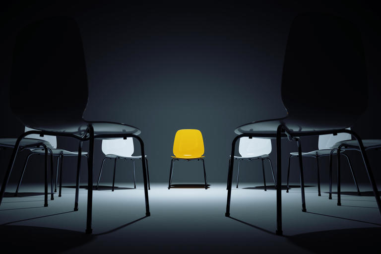 White chairs in circle with one yellow chair standing out