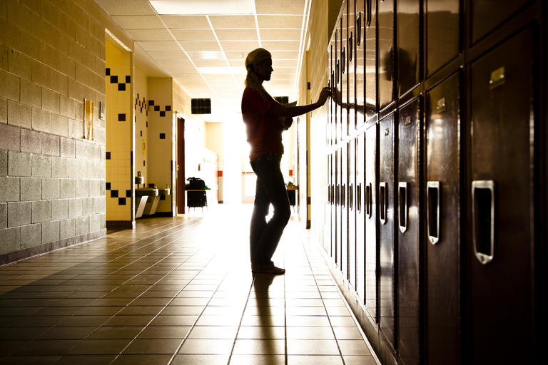 Student standing by her locker at school