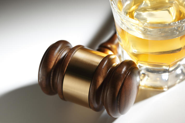 Glass of alcohol sitting next to a gavel