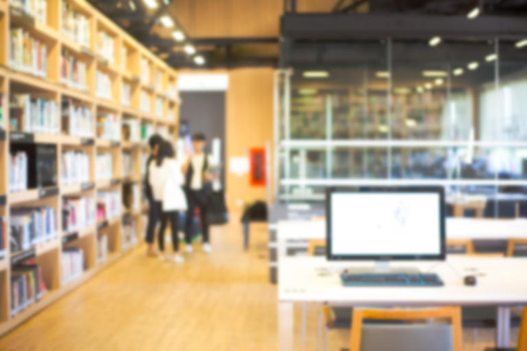 Blurred image of students in school library