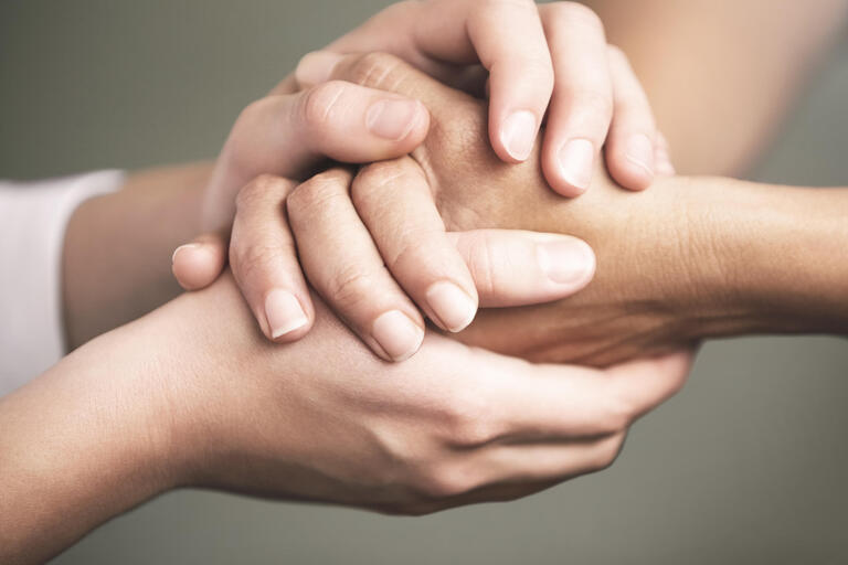 Two pairs of hands holding in firm handshake