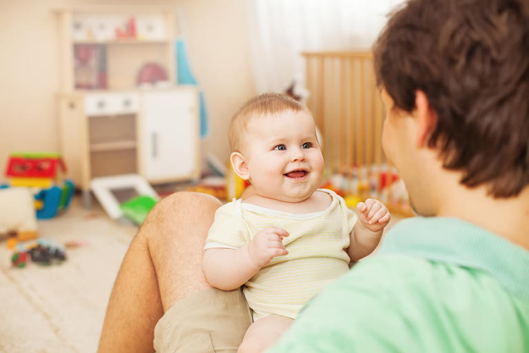 Parent talking to smiling baby