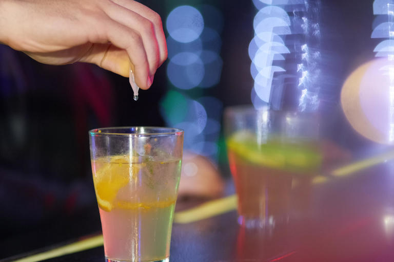 Person pouring suspicious substance into cocktail