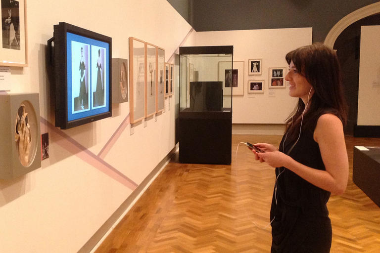 Woman looking at artwork and listening to headphones