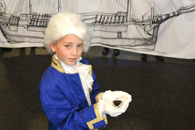 Child in costume holding Captain Cooks shoe buckle