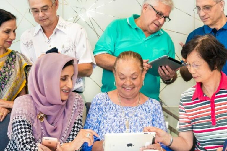 A group of older people from different cultural backgrounds learn how to use technology together
