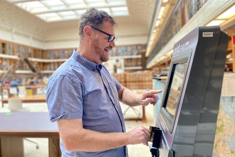 Man using Library copy card reload kiosks in Mitchell Reading Room