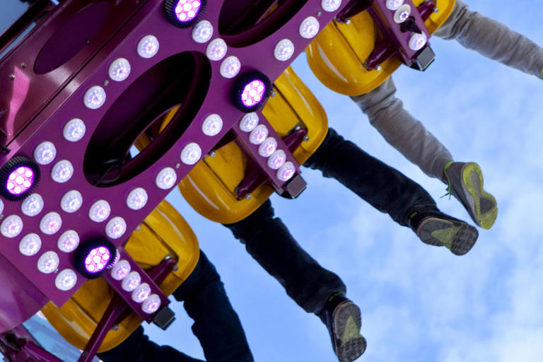 Fairground ride with legs hanging down