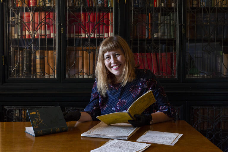 Woman sitting at a desk handling manuscript of 'Seven Little Australians' by Ethel Turner.