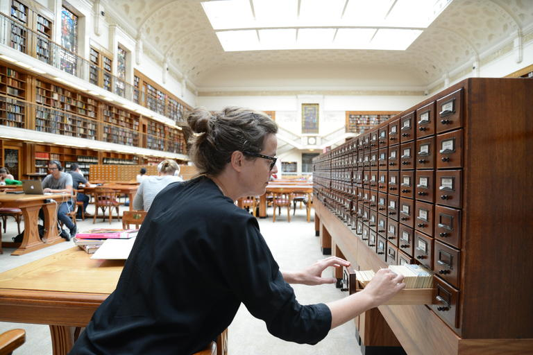 Researcher using the Mitchell Library card catalogue