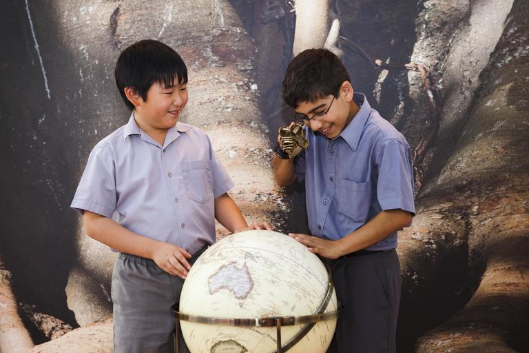 Two school boys with world globe