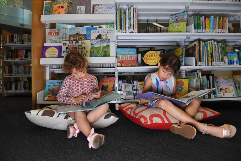 Two young girls sitting on cushions reading books.