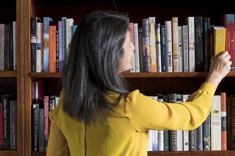 Women pulling books off shelf