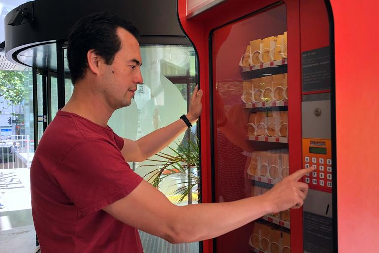 Person using the Vending Library in the Macquarie St foyer of the State Library of NSW