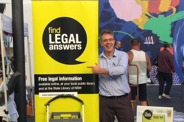 Library staff member with Find Legal Answers banner at stall in the mall event