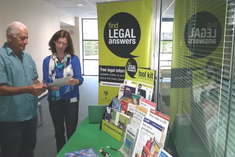 Two people looking at legal books - Law week at Sutherland library
