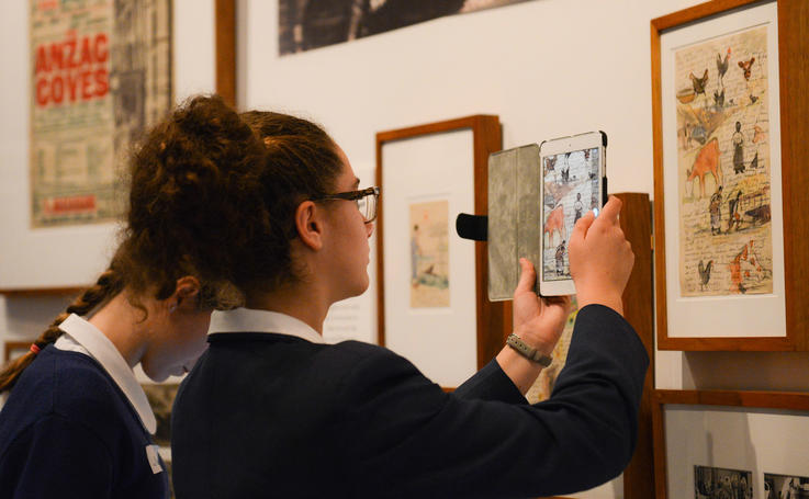Student scanning a picture on wall with her tablet