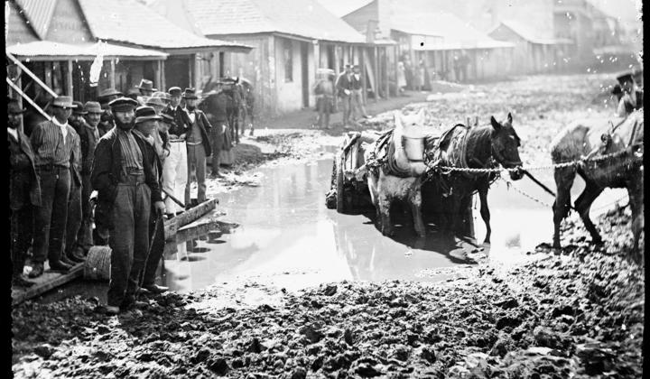 Horse and cart struggling through muddy street as men watch