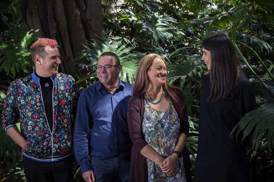 Two men and two women representing the Indigenous Engagement Branch smiling and standing in front of green plants.