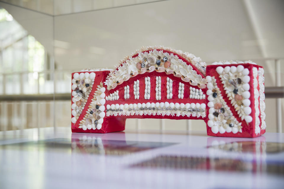 A small red bridge covered by white shells