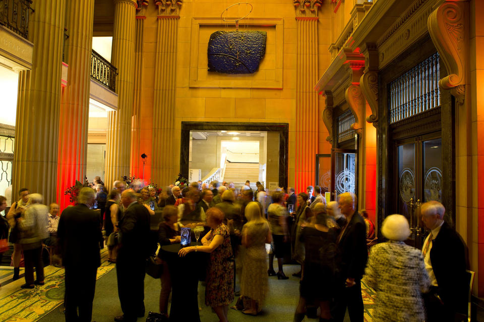 People standing and talking in large sandstone room with columns