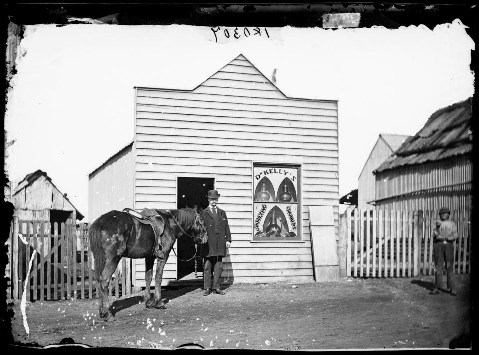 Black and white photo of a man and horse standing outside a building Dr. Kelly's consulting chambers, Mayne St. West, Gulgong