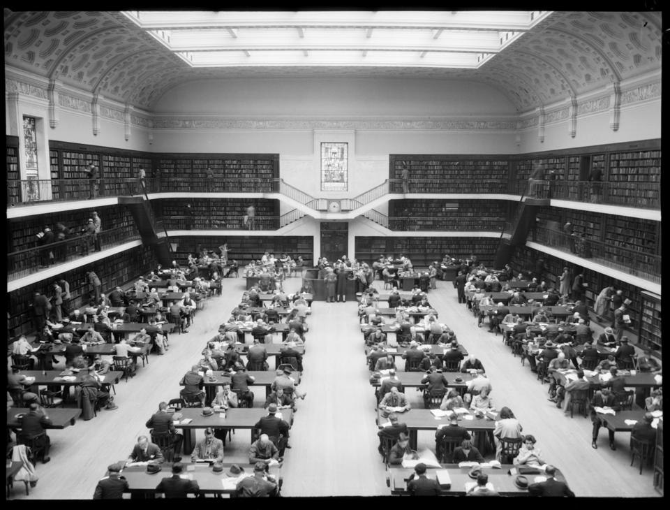 Large room in Library with glass ceiling and books shelves around the circumference of the room. People at desks reading.