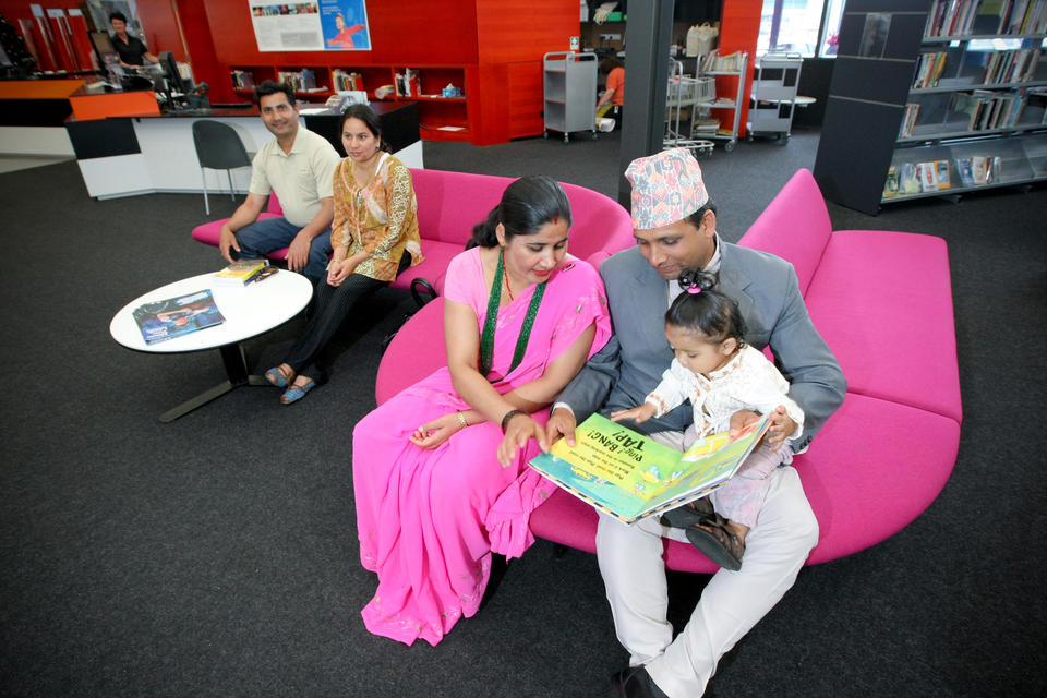 Family sitting in a library reading a picture book