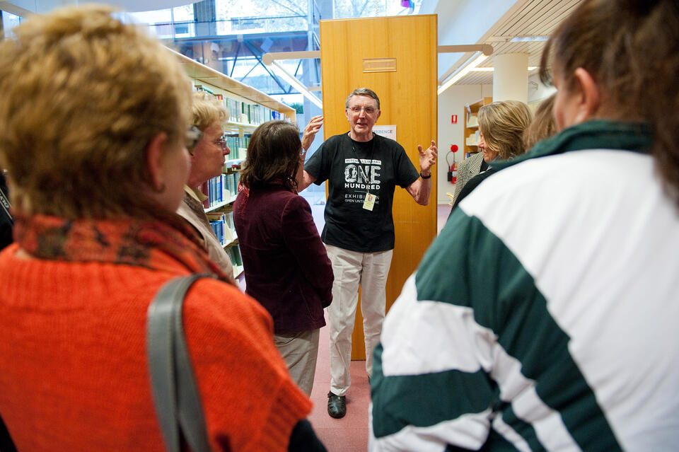 man talking to small group of people in front of bookshelves