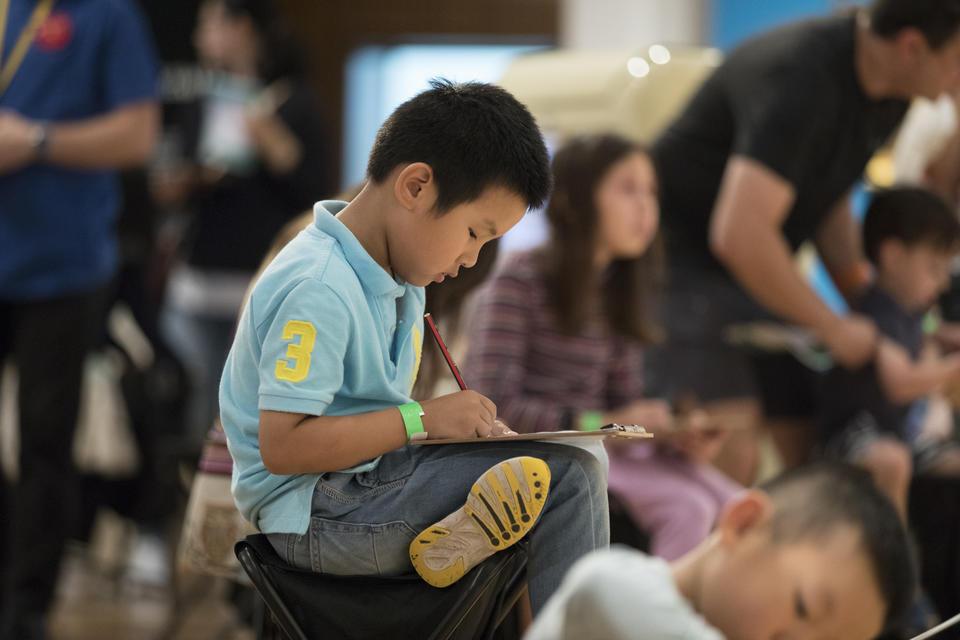 A boy, drawing on a clipboard