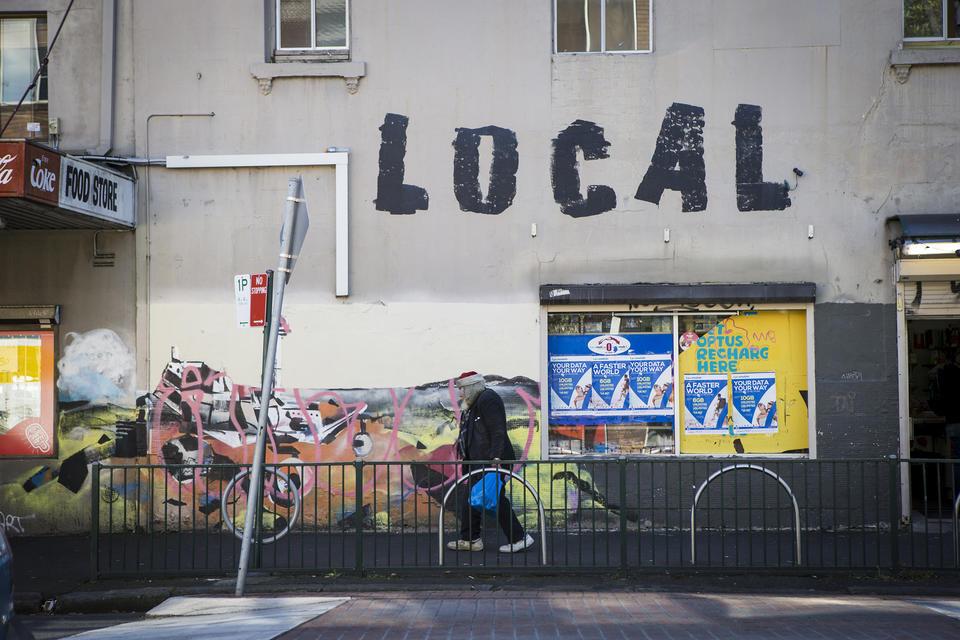 A colour photograph of a man wearing an old santa hat walking down a grafitied urban street.