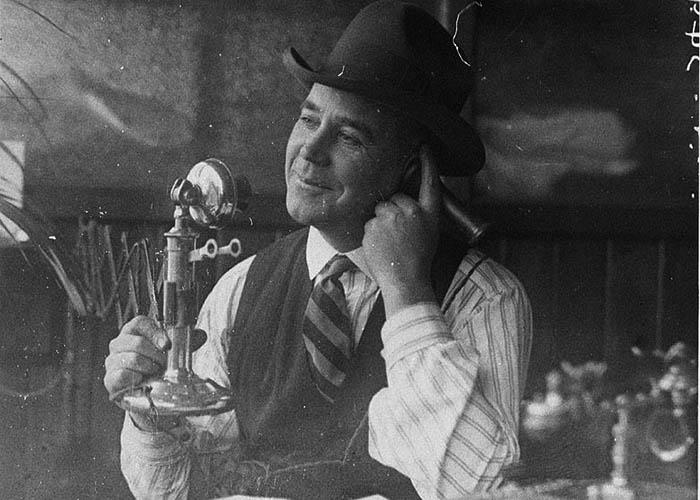 Black and white photo of man talking on vintage telephone