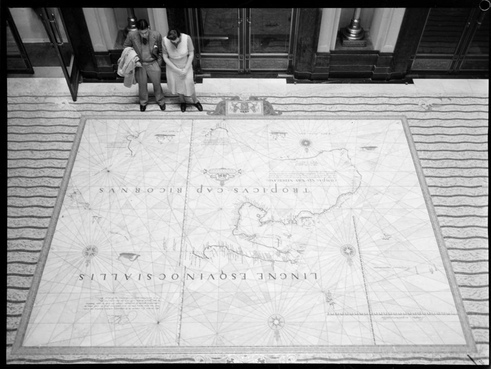Two visitors look at the Tasman Map floor at the State Library.