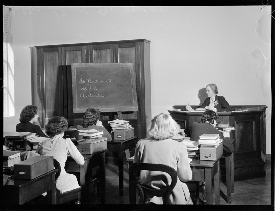 A classroom of women, facing a female teacher at a podium and a chalkboard.